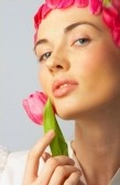 Fashion shot of a beautiful, professional model with pink flowers.